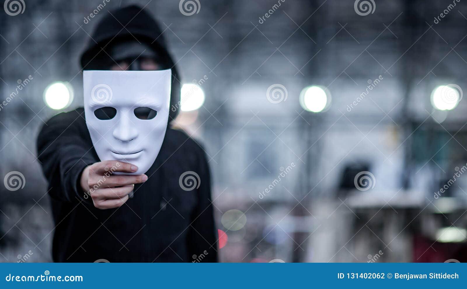 Homme de hoodie de mystère avec le masque noir tenant le masque blanc dans sa main Concept social anonyme de masquage ou de troub