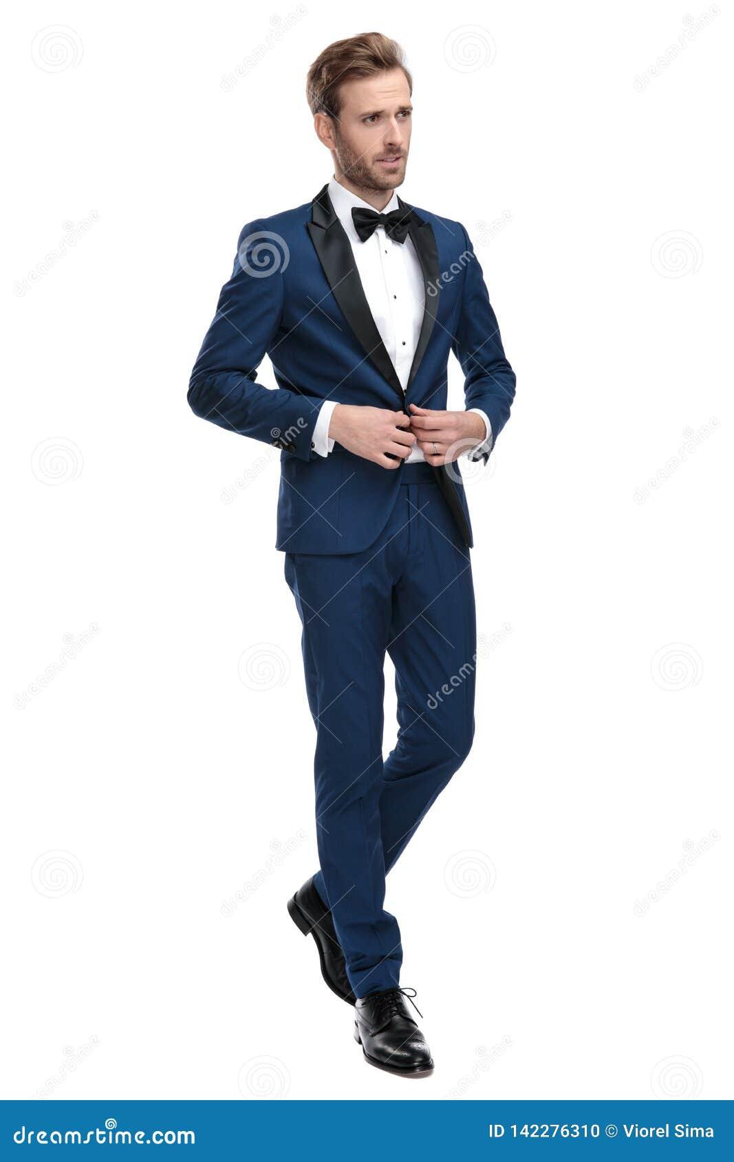 Homme de mode dans le costume bleu boutonnant sa veste de salon