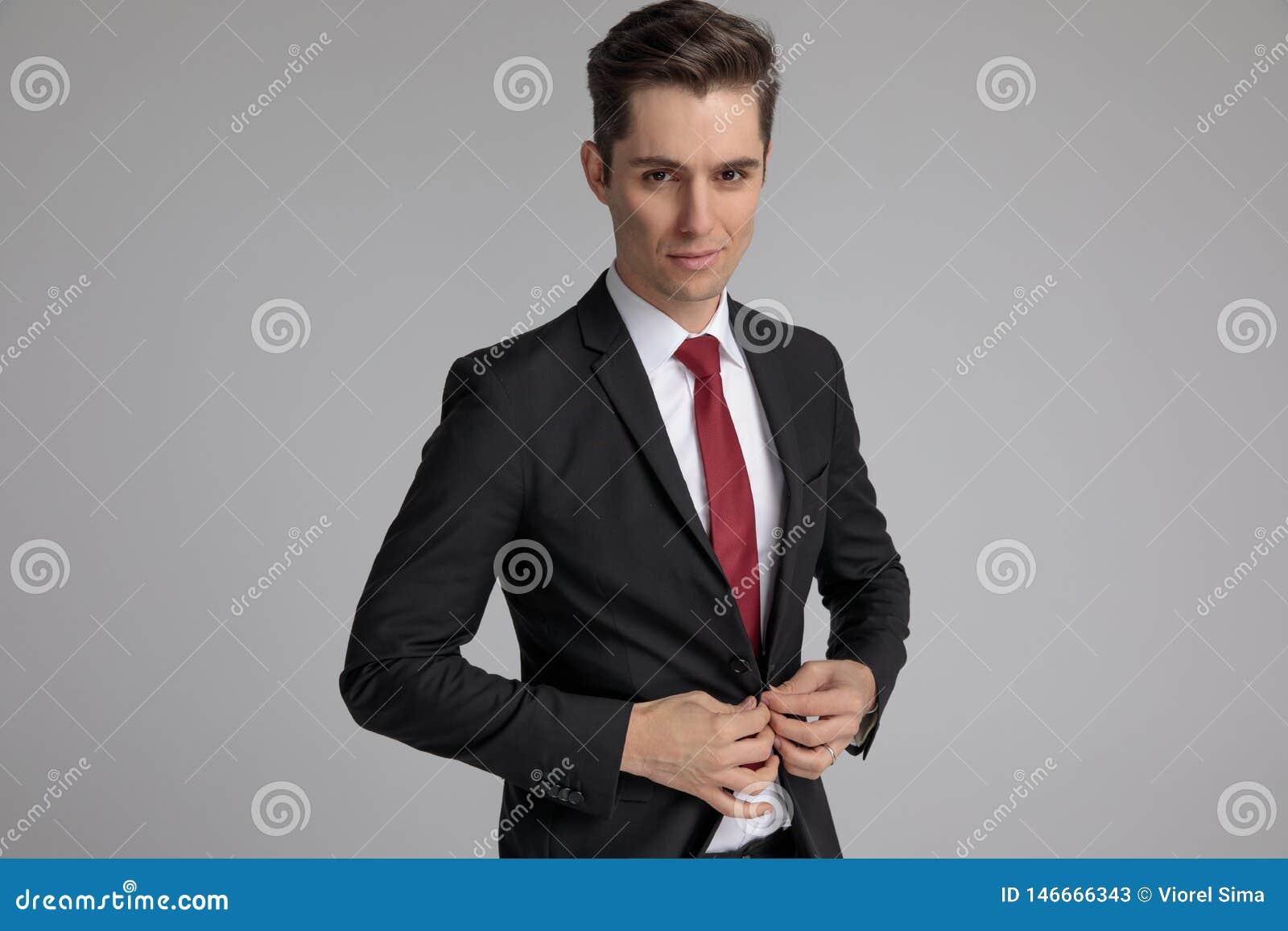 Homme de mode dans le costume noir boutonnant sa veste de salon