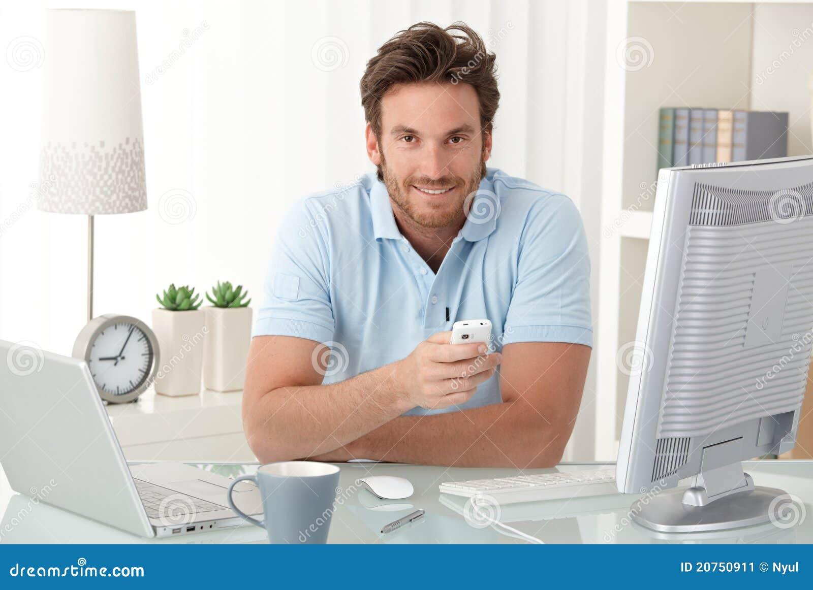 Homme de sourire au bureau avec le t l phone portable for Bureau homme