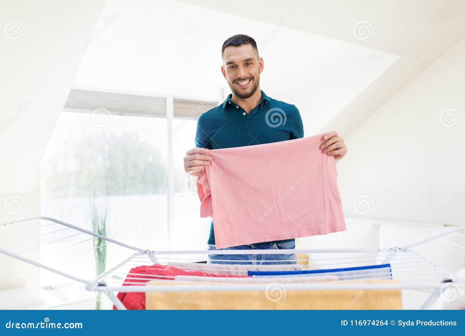 Homme de sourire avec la blanchisserie et le support de séchage à la maison