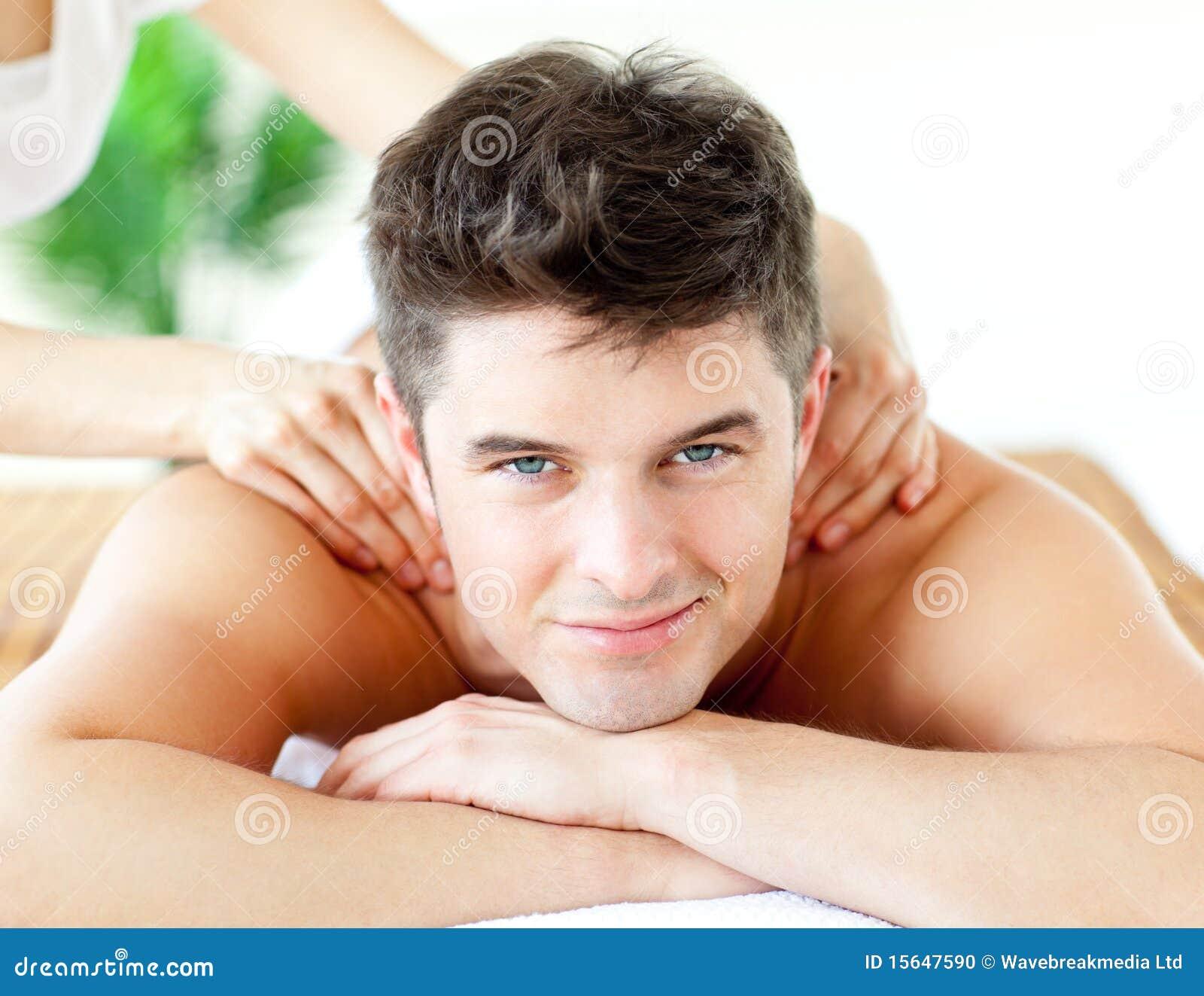 Homme de sourire bel appréciant un massage arrière