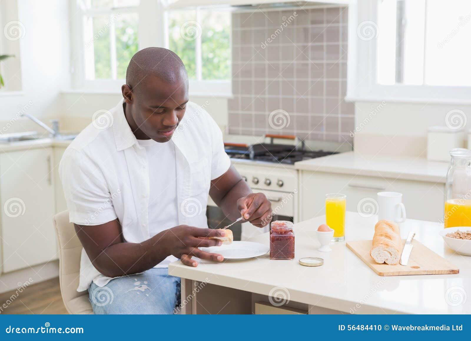 Homme de sourire prenant son petit déjeuner