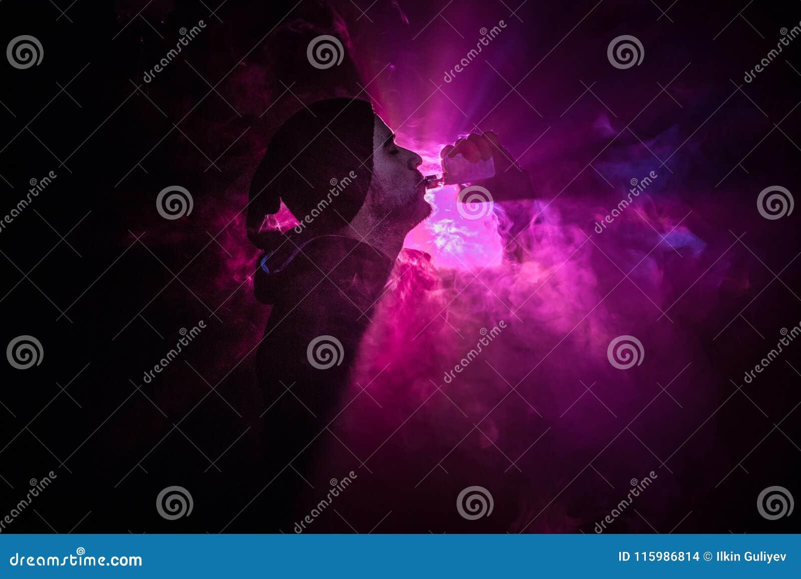 Homme de Vaping tenant un mod Un nuage de vapeur Fond noir Vaping une cigarette électronique avec de la beaucoup de fumée Concept