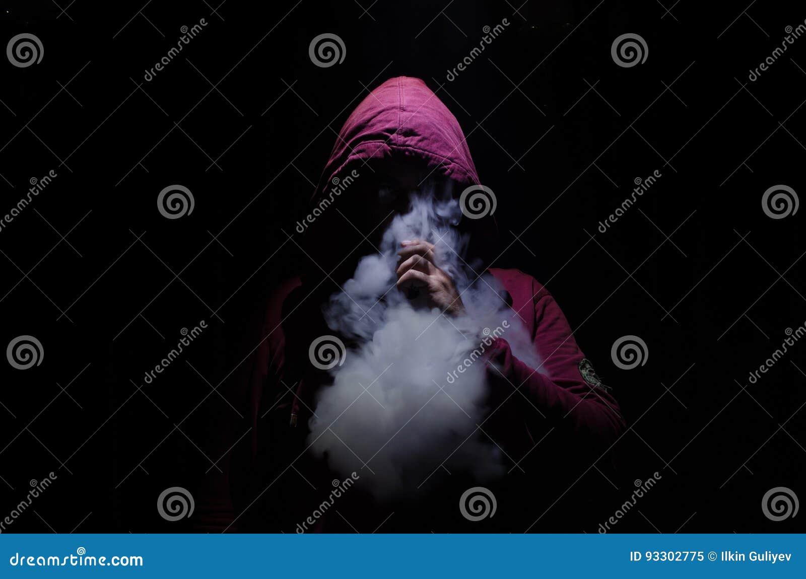Homme de Vaping tenant un mod Un nuage de vapeur Fond noir Vaping une cigarette électronique avec de la beaucoup de fumée