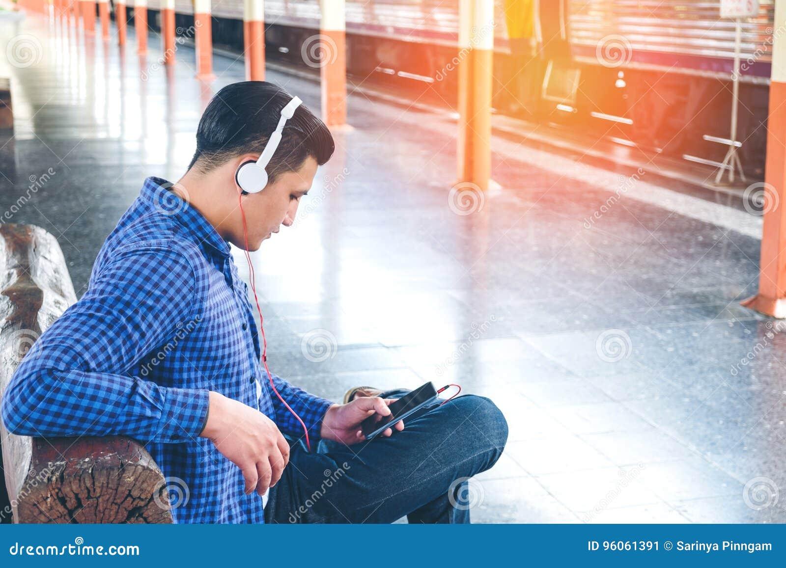 Homme de voyageur à l aide du train de attente de comprimé et d écouteur sur