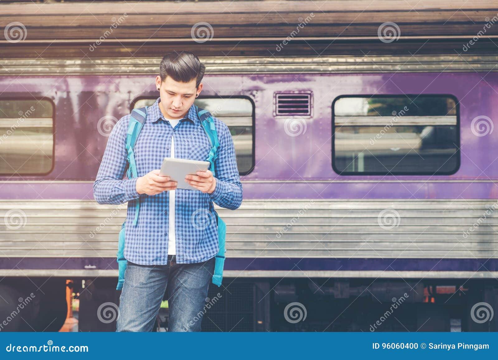 Homme de voyageur à l aide du train de attente de comprimé et de téléphone sur le sta