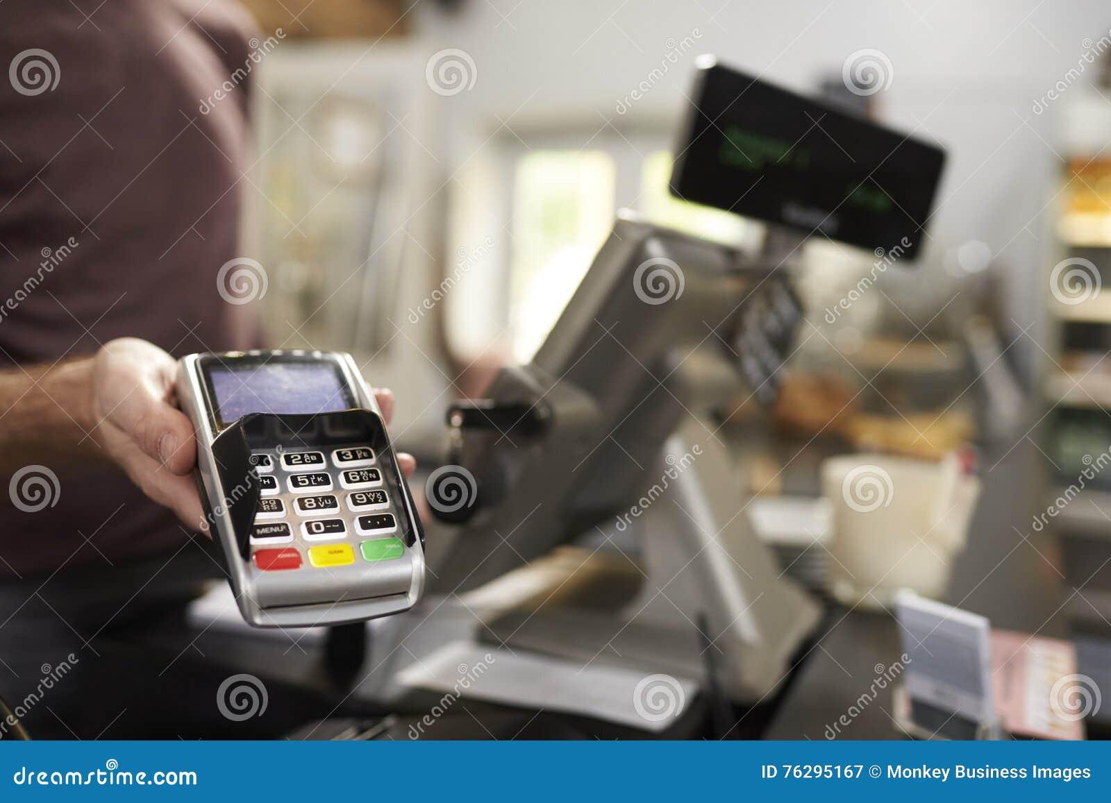 Homme derrière le compteur sur un terminal de offre de carte de crédit de café