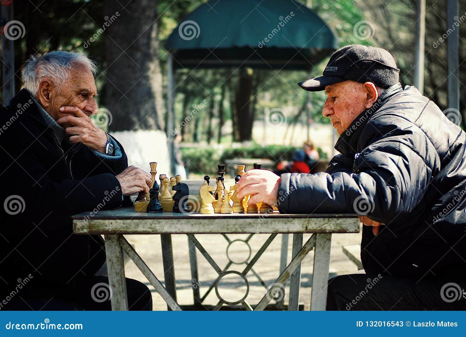 Homme deux plus âgé supérieur jouant aux échecs en parc public