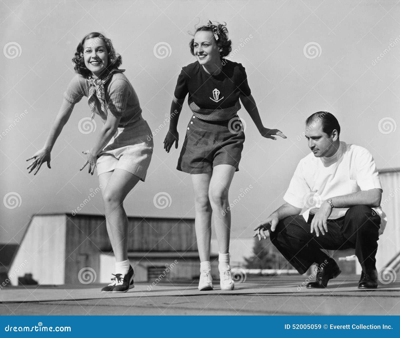 Homme donnant des leçons particulières à deux danseurs féminins