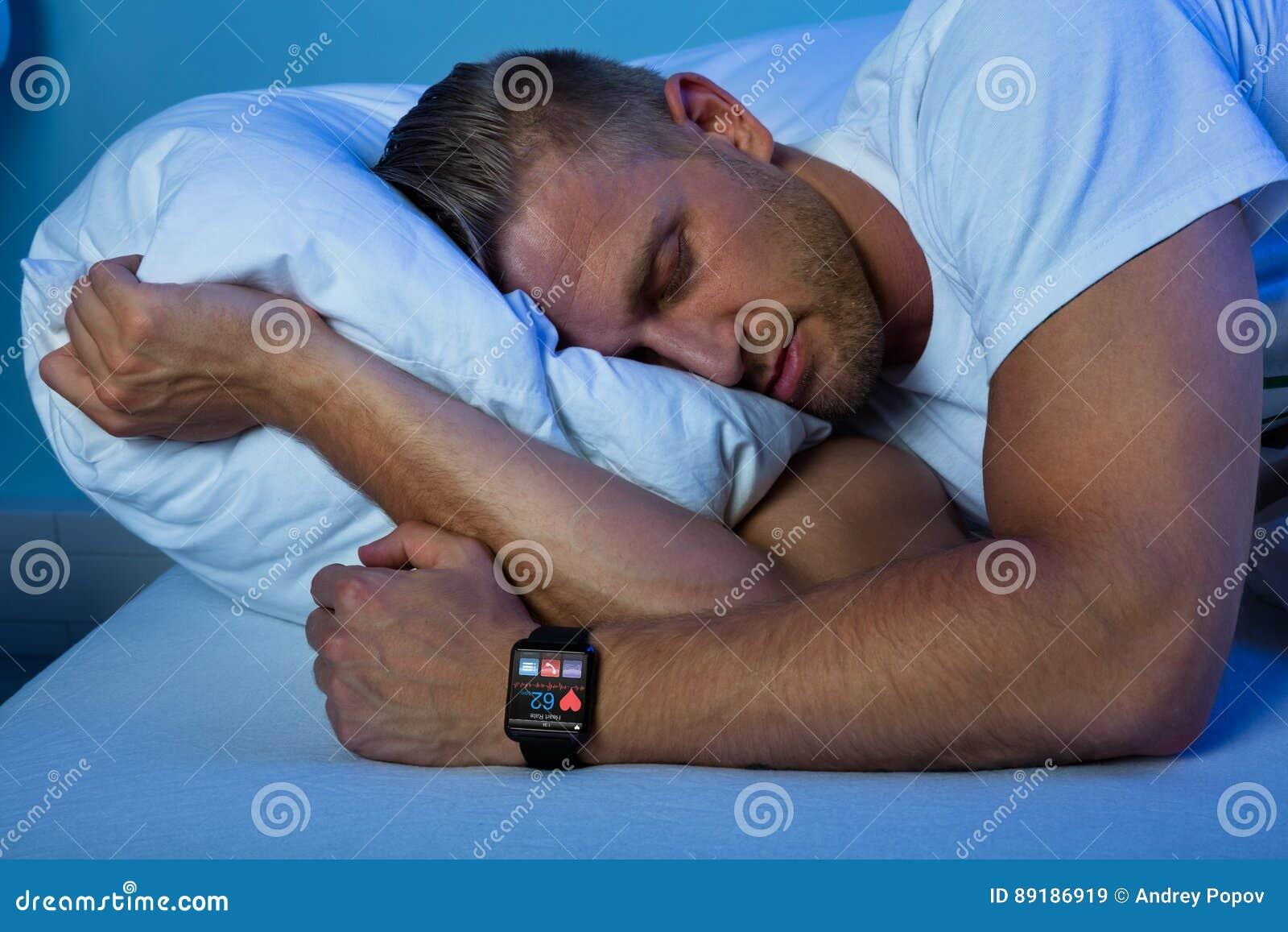 Homme dormant avec la montre intelligente dans sa main