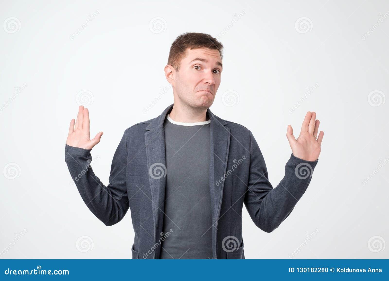 Homme douteux avec l expression réfléchie faisant le choix dans le studio d isolement sur le mur blanc