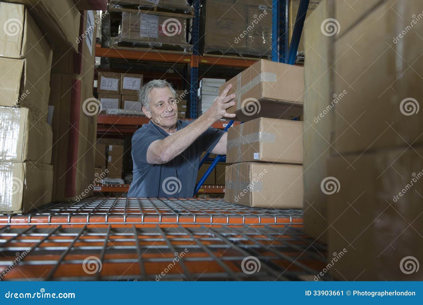 Homme empilant des boîtes dans l entrepôt