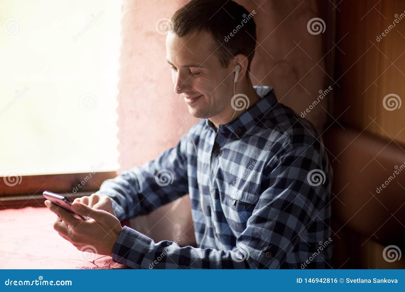Homme employant l application mobile sur son smartphone ? la station de train, voyage d affaires