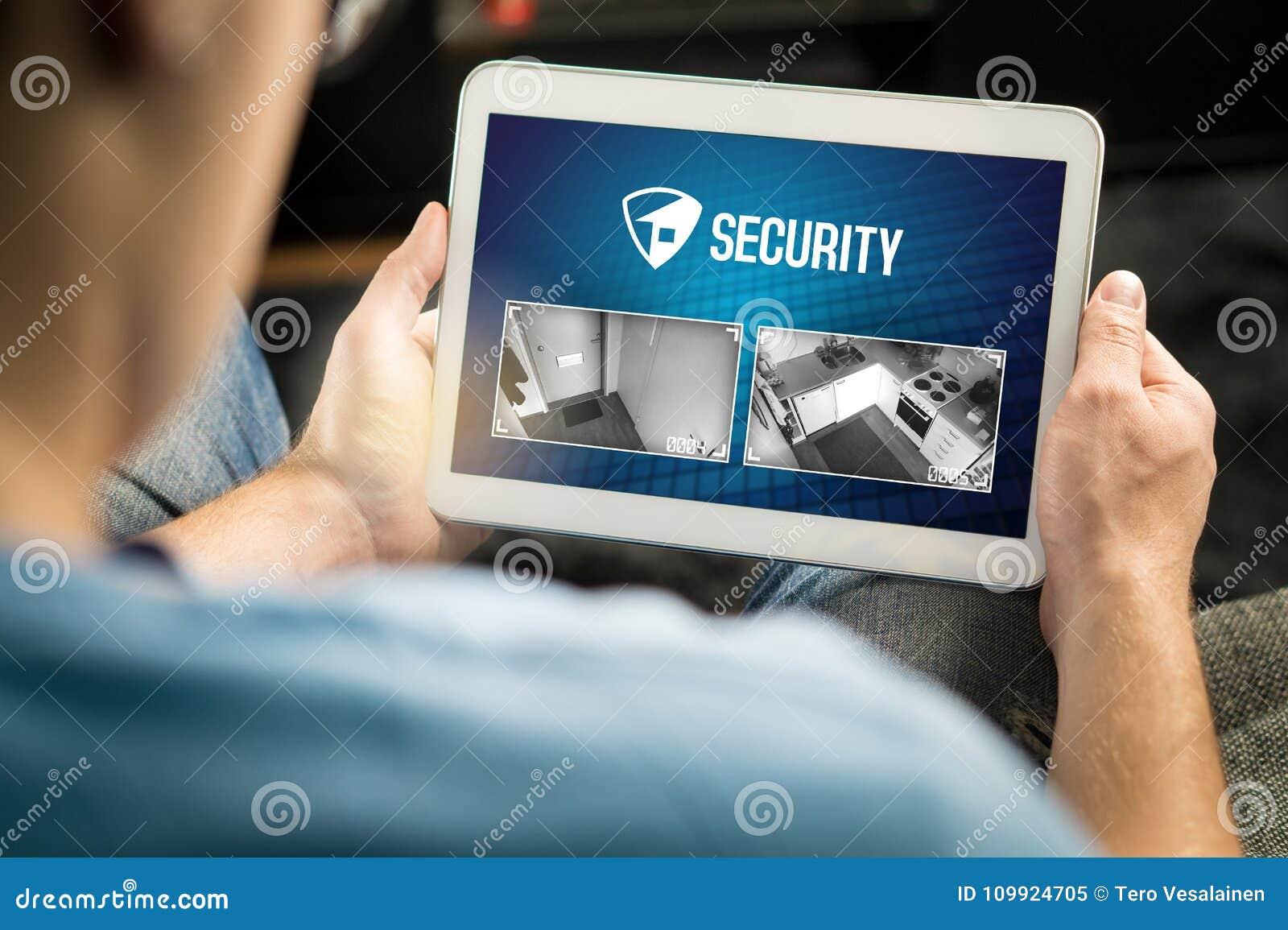 Homme employant le système de sécurité et l application à la maison dans le comprimé