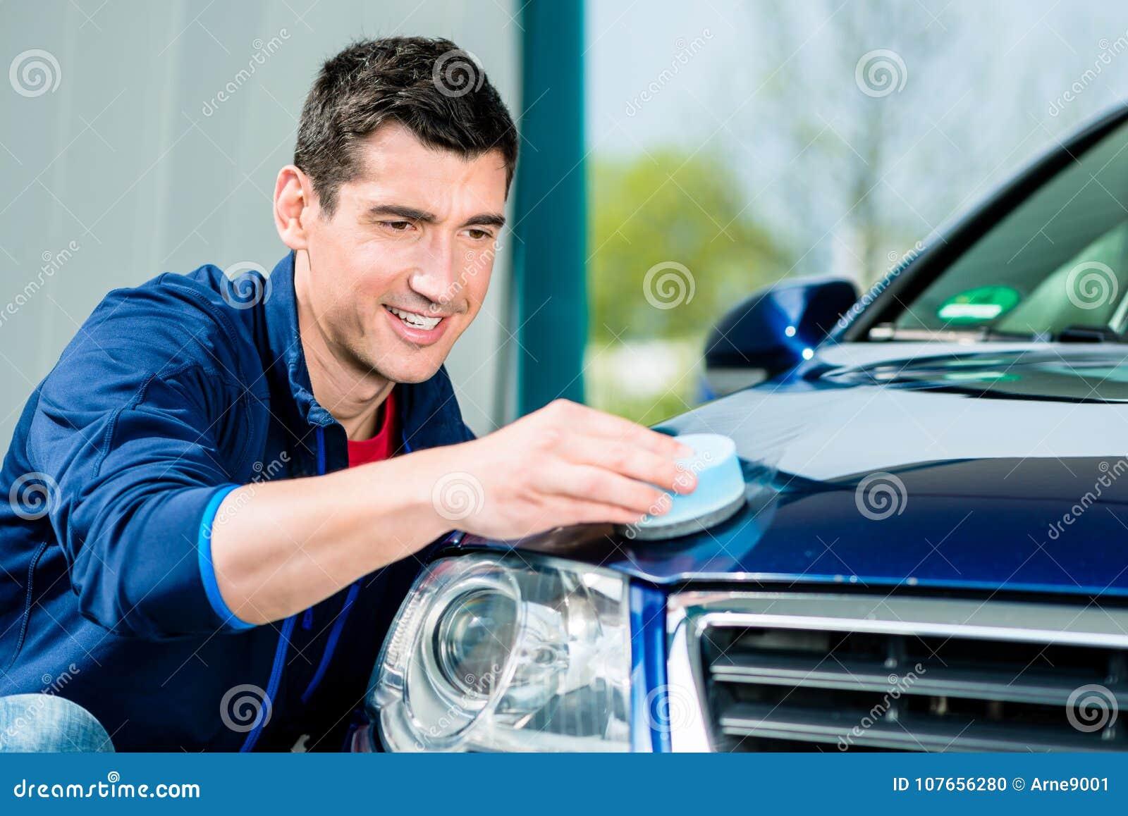 Homme employant une serviette absorbante pour sécher la surface d une voiture