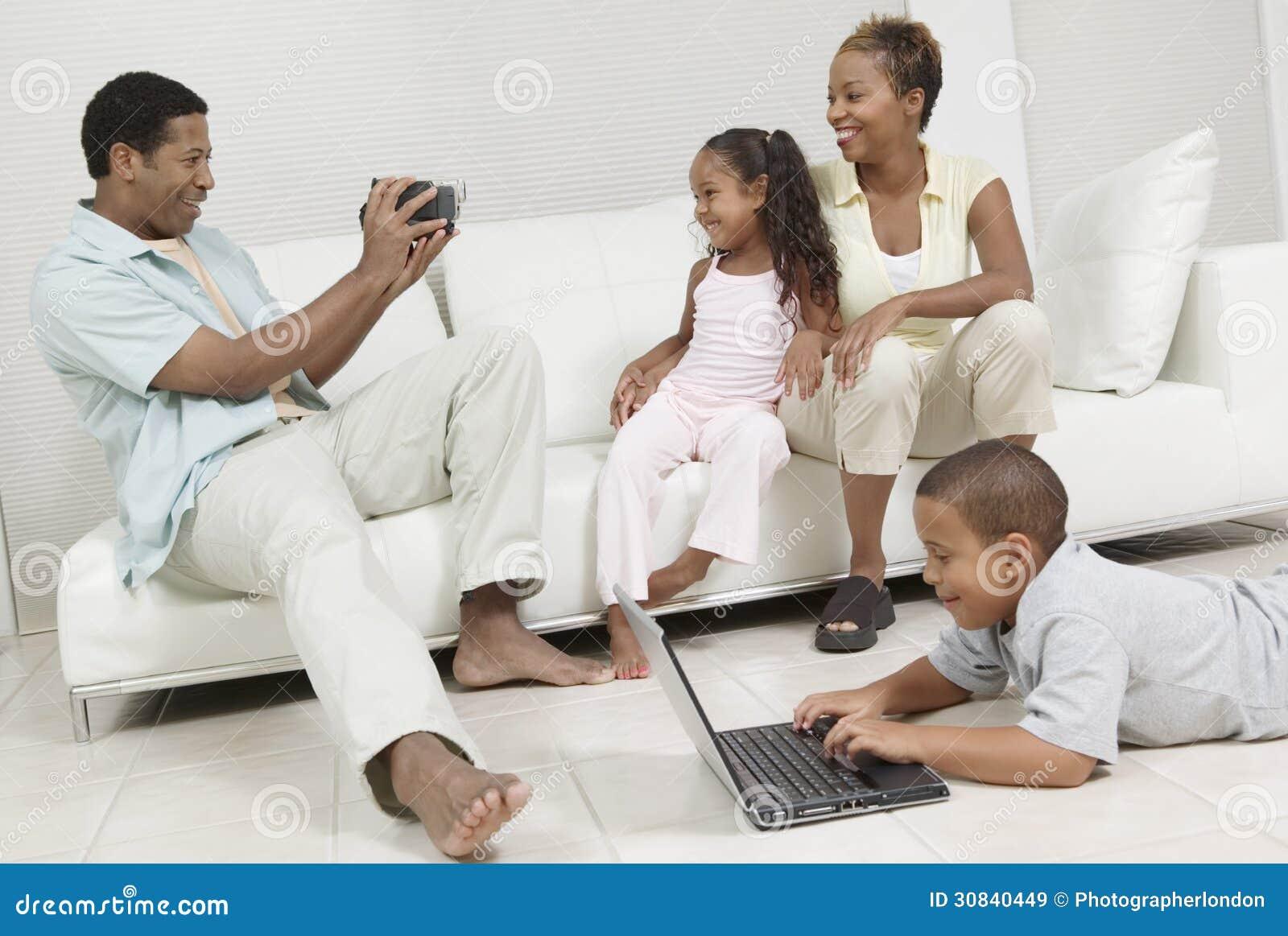 Homme enregistrant la famille en vidéo s asseyant sur le sofa