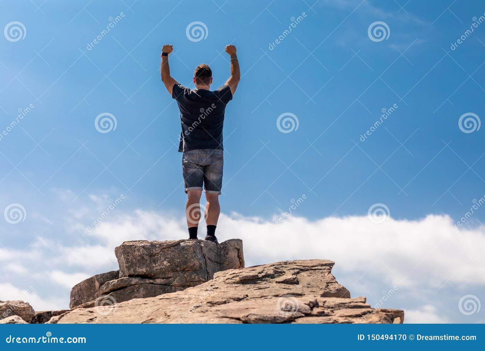 Homme enthousiaste sur le dessus dans un beau paysage d été