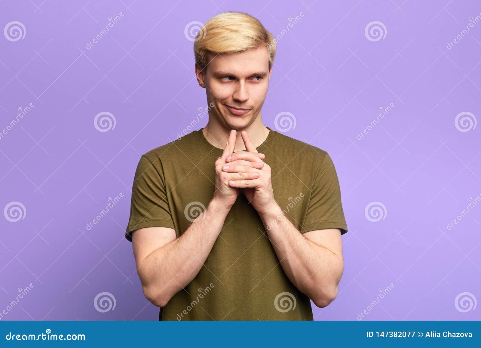 Homme espiègle adroit astucieux touchant le menton avec le doigt et regardant loin