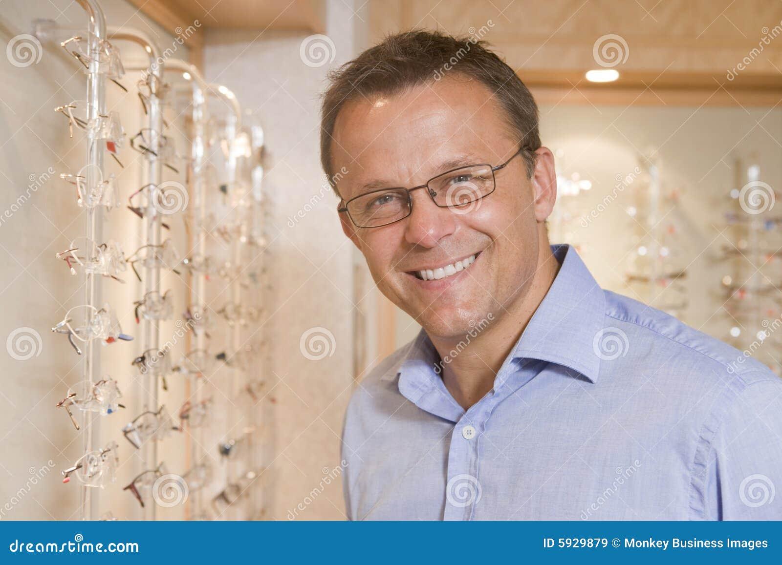 Homme essayant sur des lunettes aux optométristes