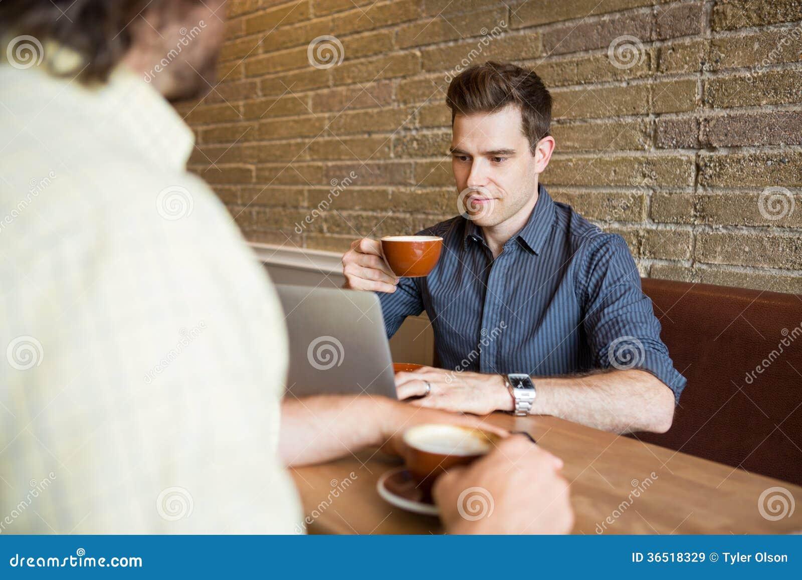 Homme et ami dans le café utilisant l ordinateur