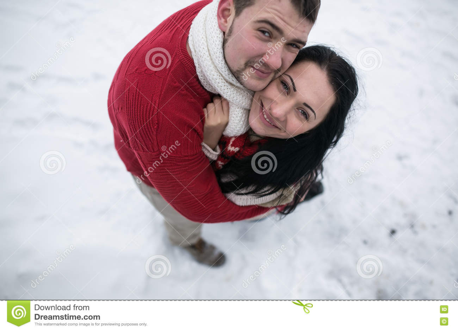 Homme et femme étreignant en parc couvert de neige