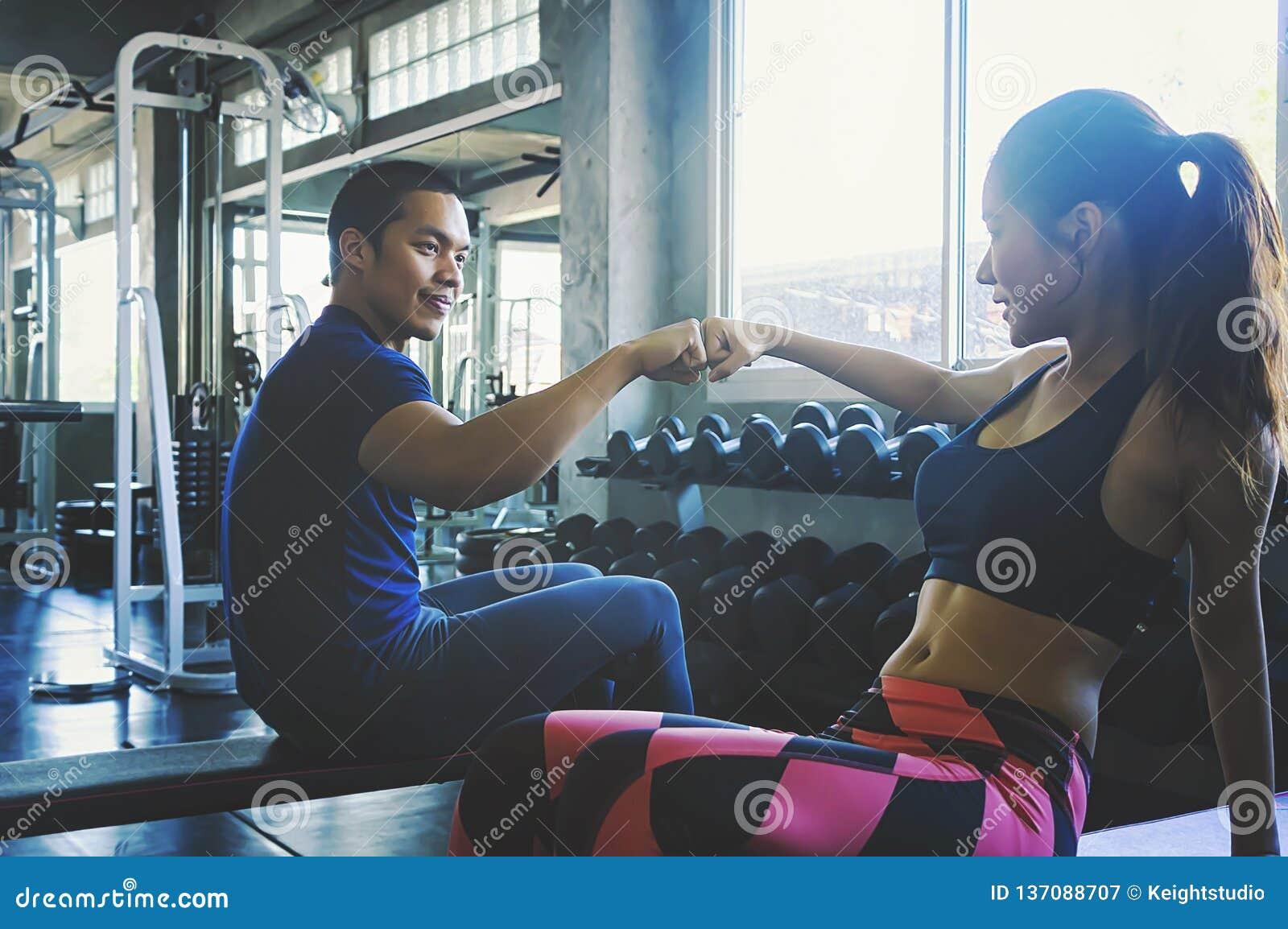 Homme et femme de forme physique se donnant de hauts cinq après le stage de formation dans le gymnase Couples convenables hauts c