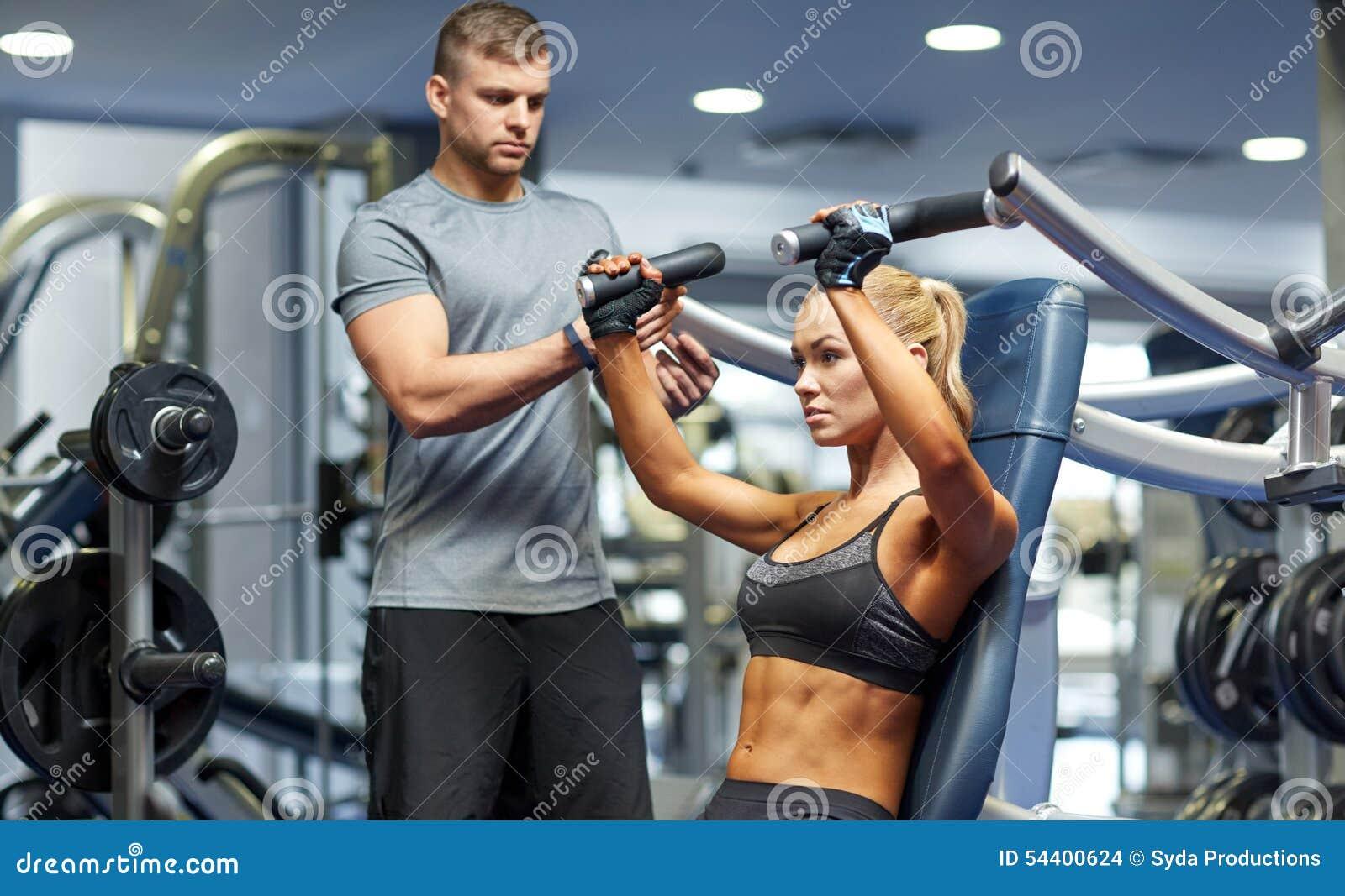 Homme et femme fléchissant des muscles sur la machine de gymnase