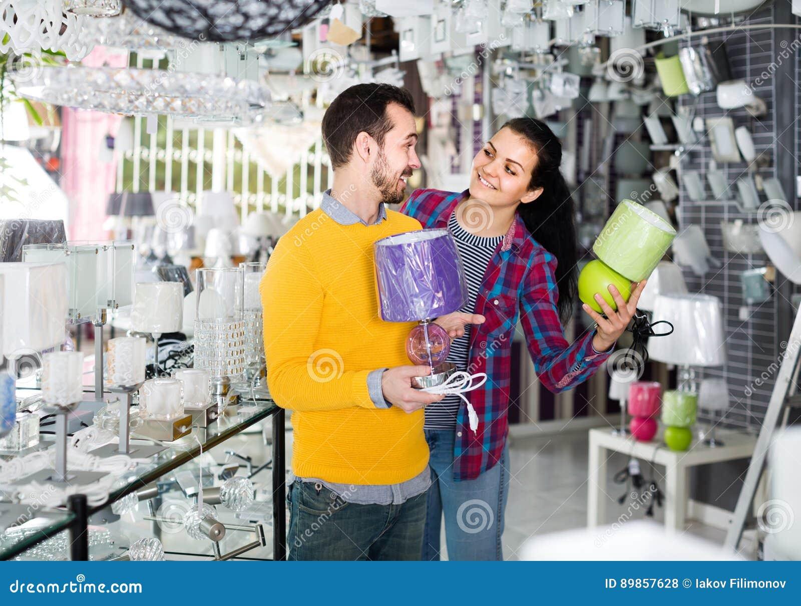 Homme et fille dans une boutique plus légère discutant l achat de la lampe de chevet