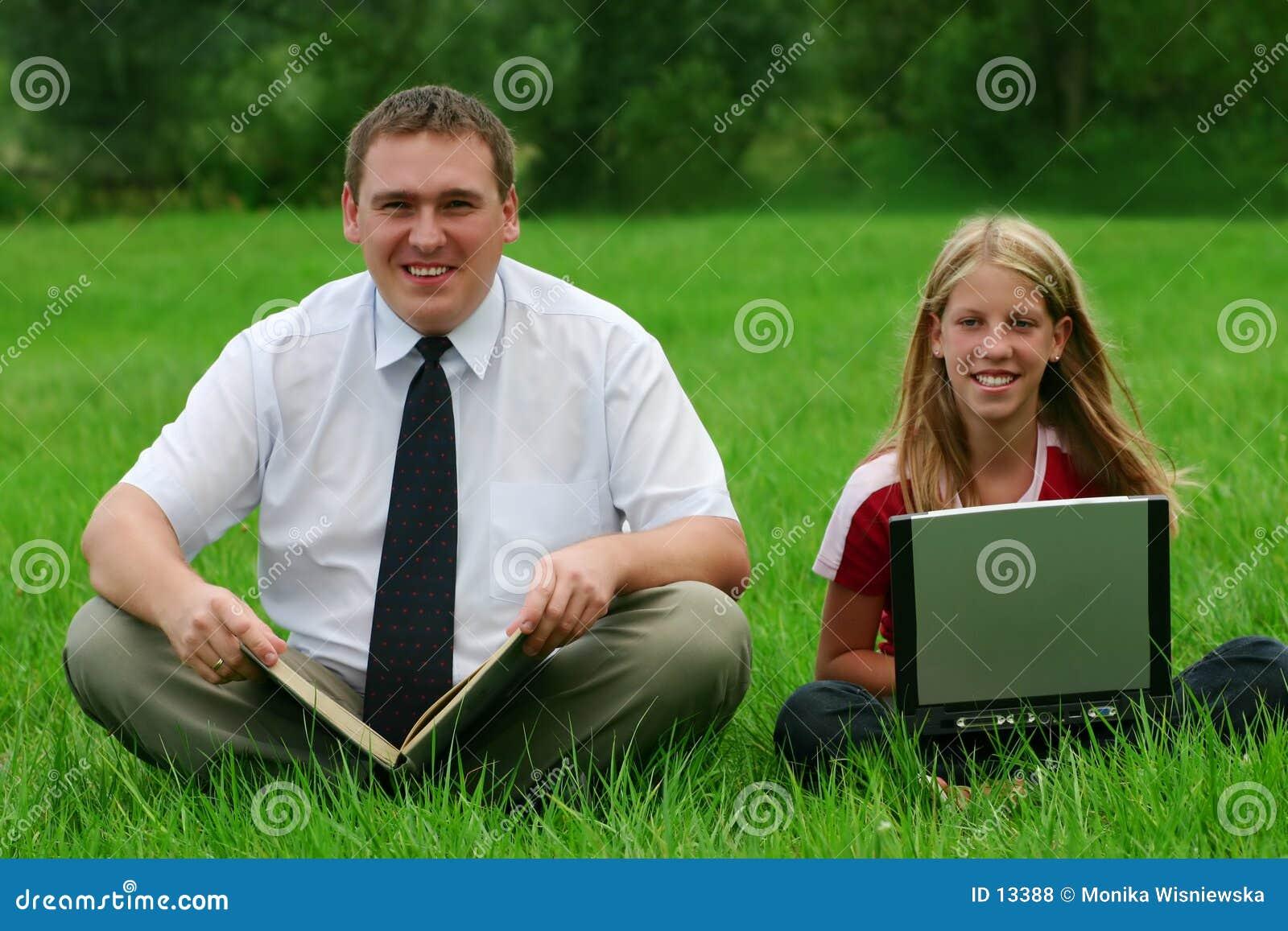 Homme et fille s asseyant sur l herbe