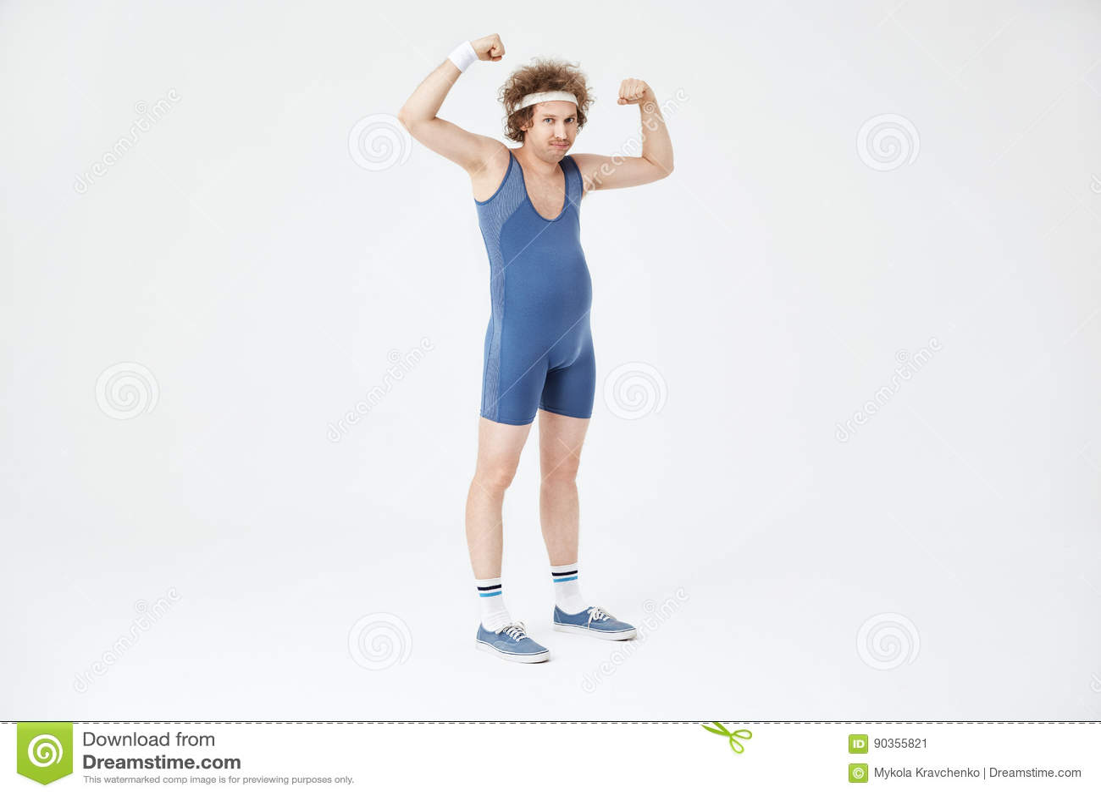 Homme faible avec le ventre montrant des muscles, posant dans la salopette de sport