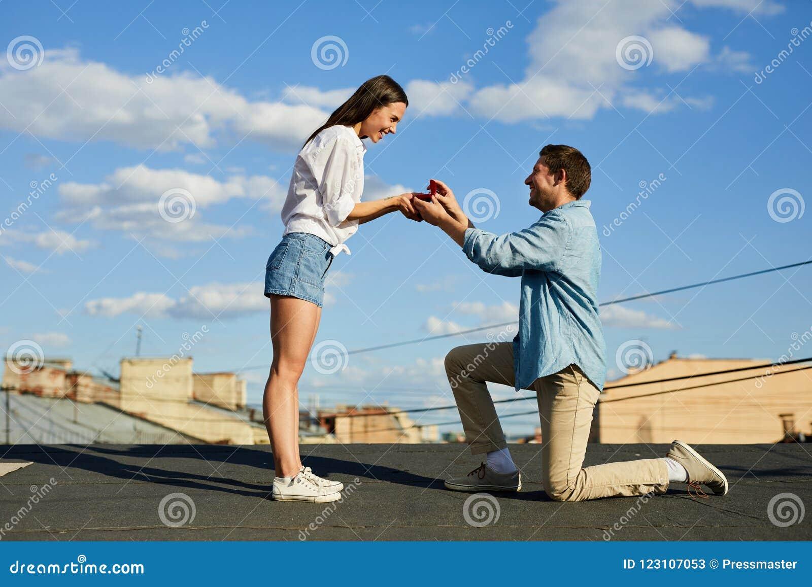 Homme faisant la proposition de mariage sur le toit