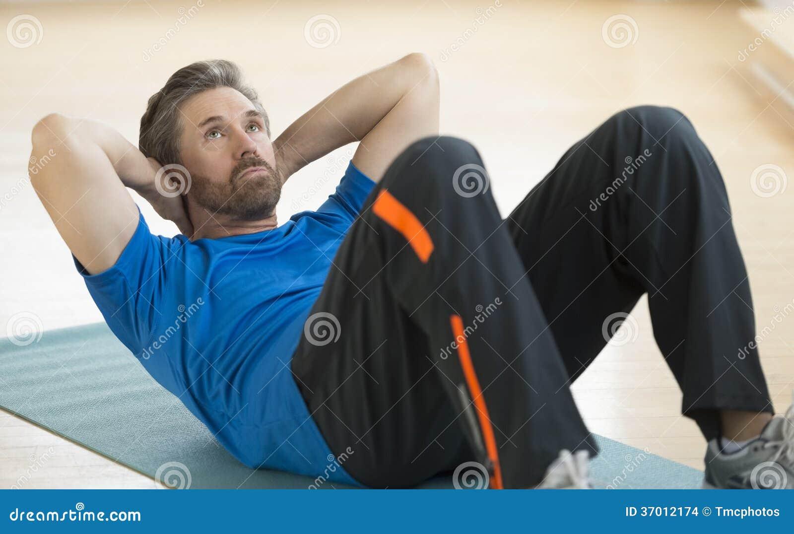 Homme faisant Reposer-UPS sur le tapis d exercice