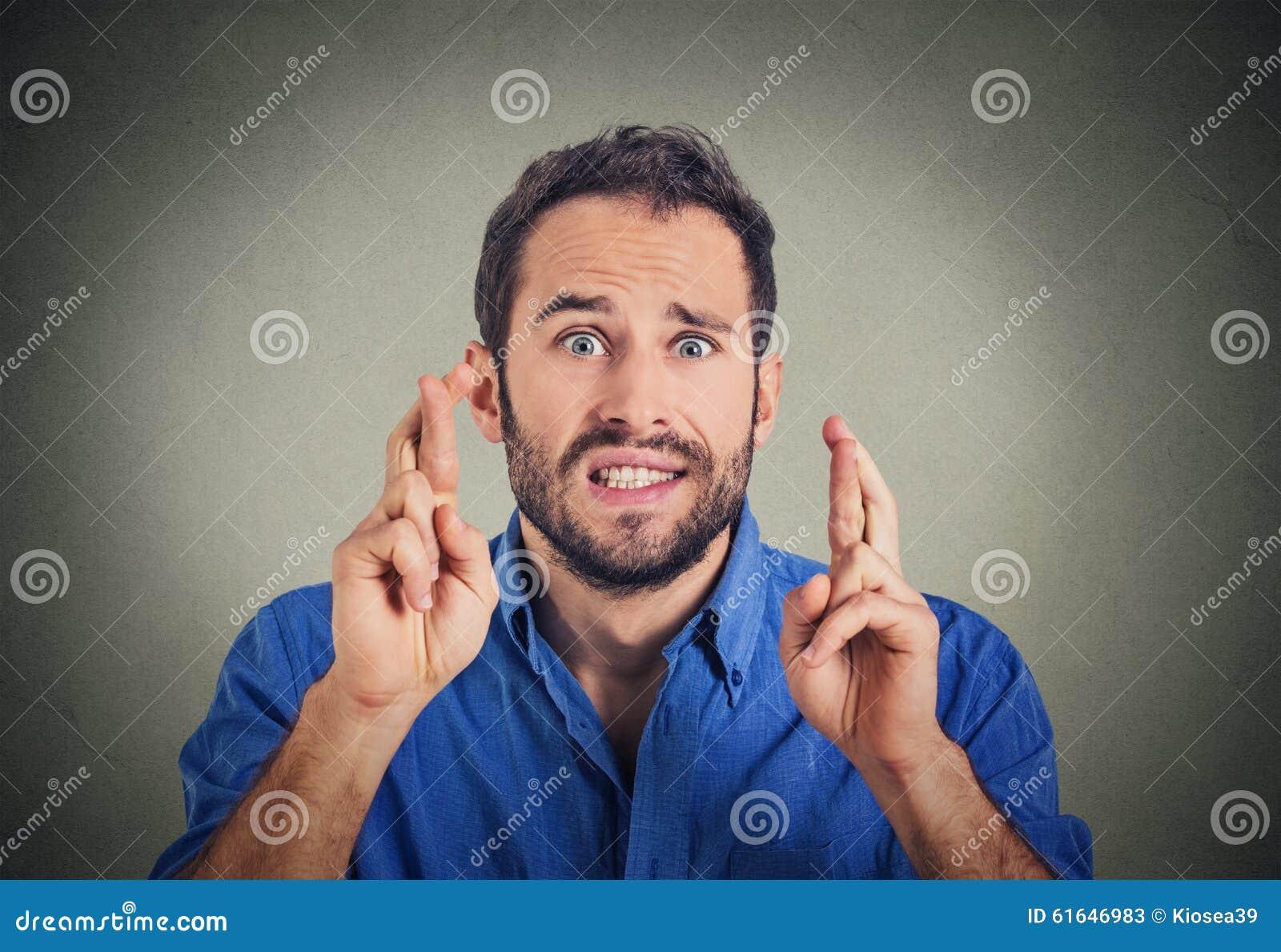 Homme faisant un souhait croisant ses doigts