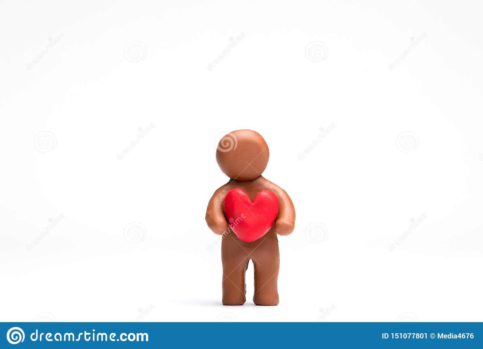 Homme fait à partir de la pâte à modeler tenant un coeur sur le fond blanc, aligné au centre