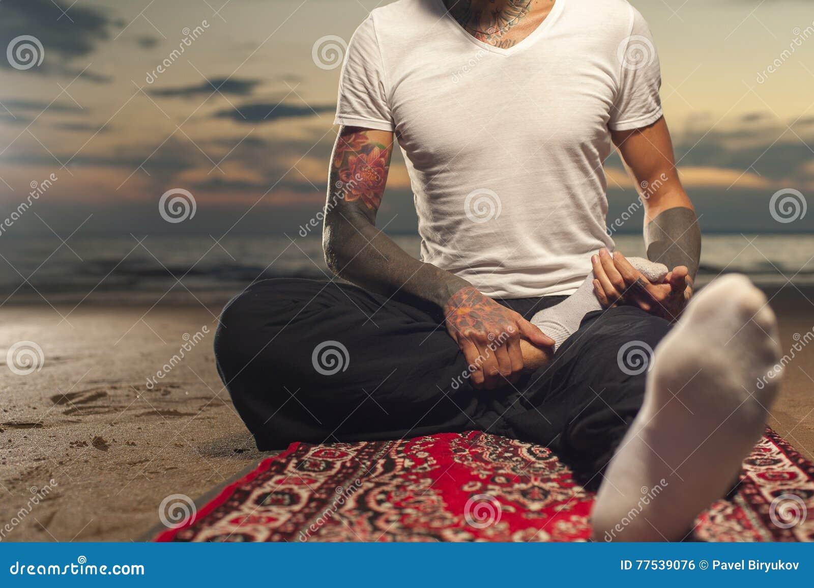 Homme Flexible Avec Le Tatouage Faisant La Pose De Lotus De Yoga