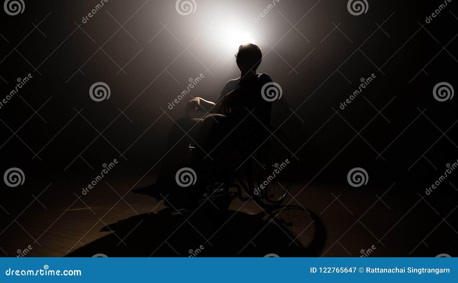 Homme foncé de silhouette sur le fauteuil roulant à l étape de mystère la production et la cinématographie visuelles avec le film