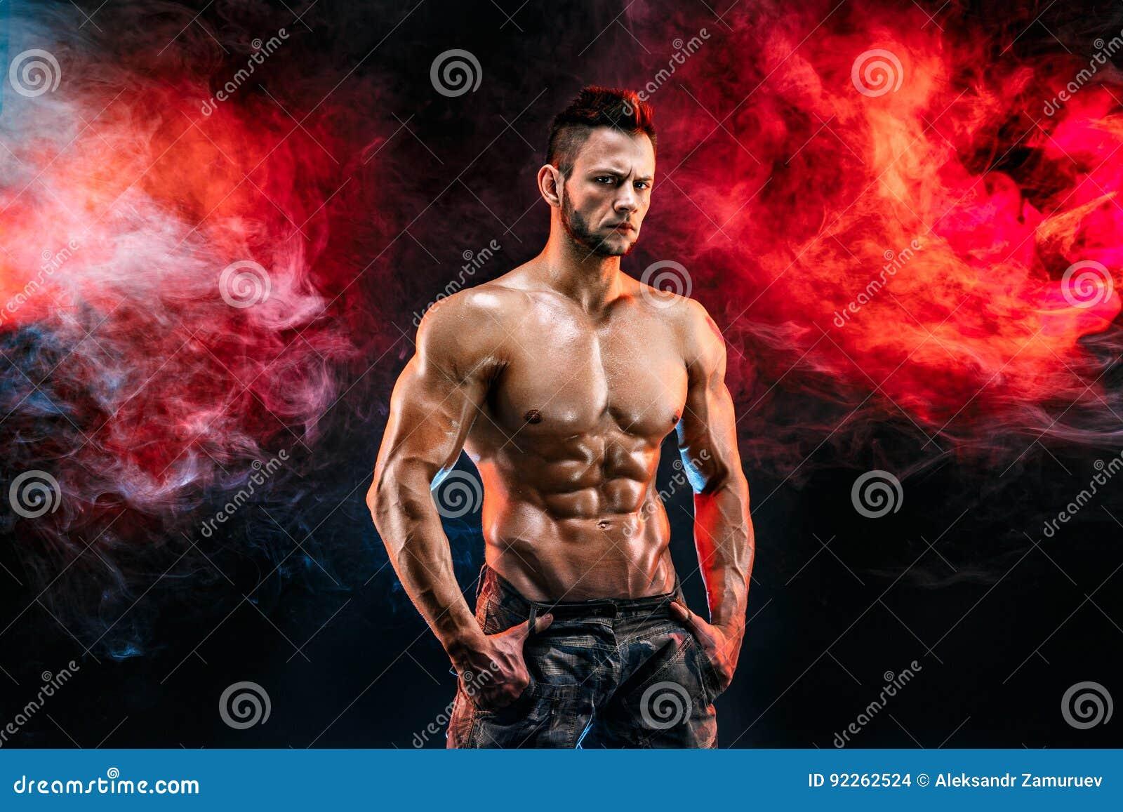 Homme fort de bodybuilder dans le pantalon militaire avec des ABS parfaits, épaules, biceps, triceps, coffre