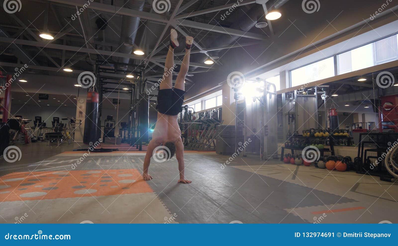 Homme fort marchant en main pendant la formation de crossfit dans le centre de fitness