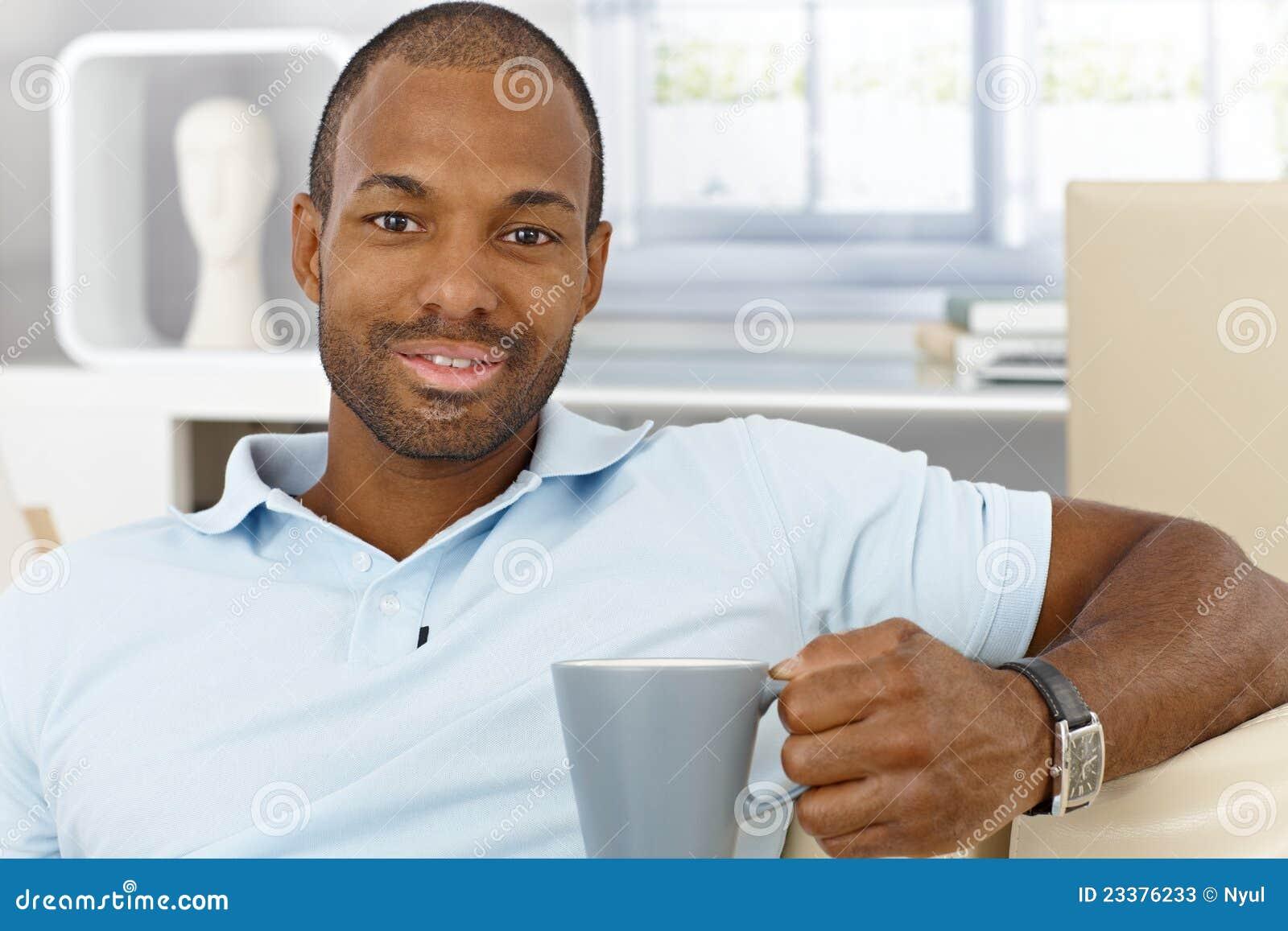 Homme gai à la maison ayant le thé