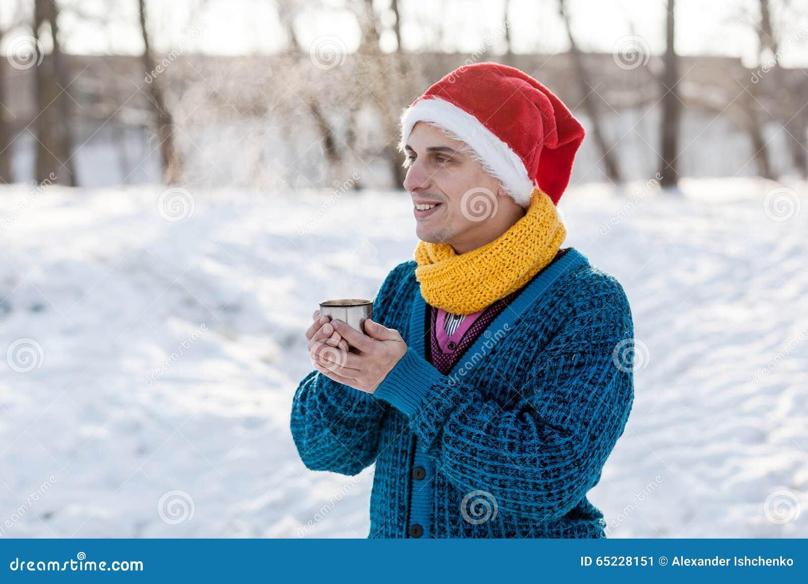 Homme gai buvant du thé chaud avec la vapeur extérieure