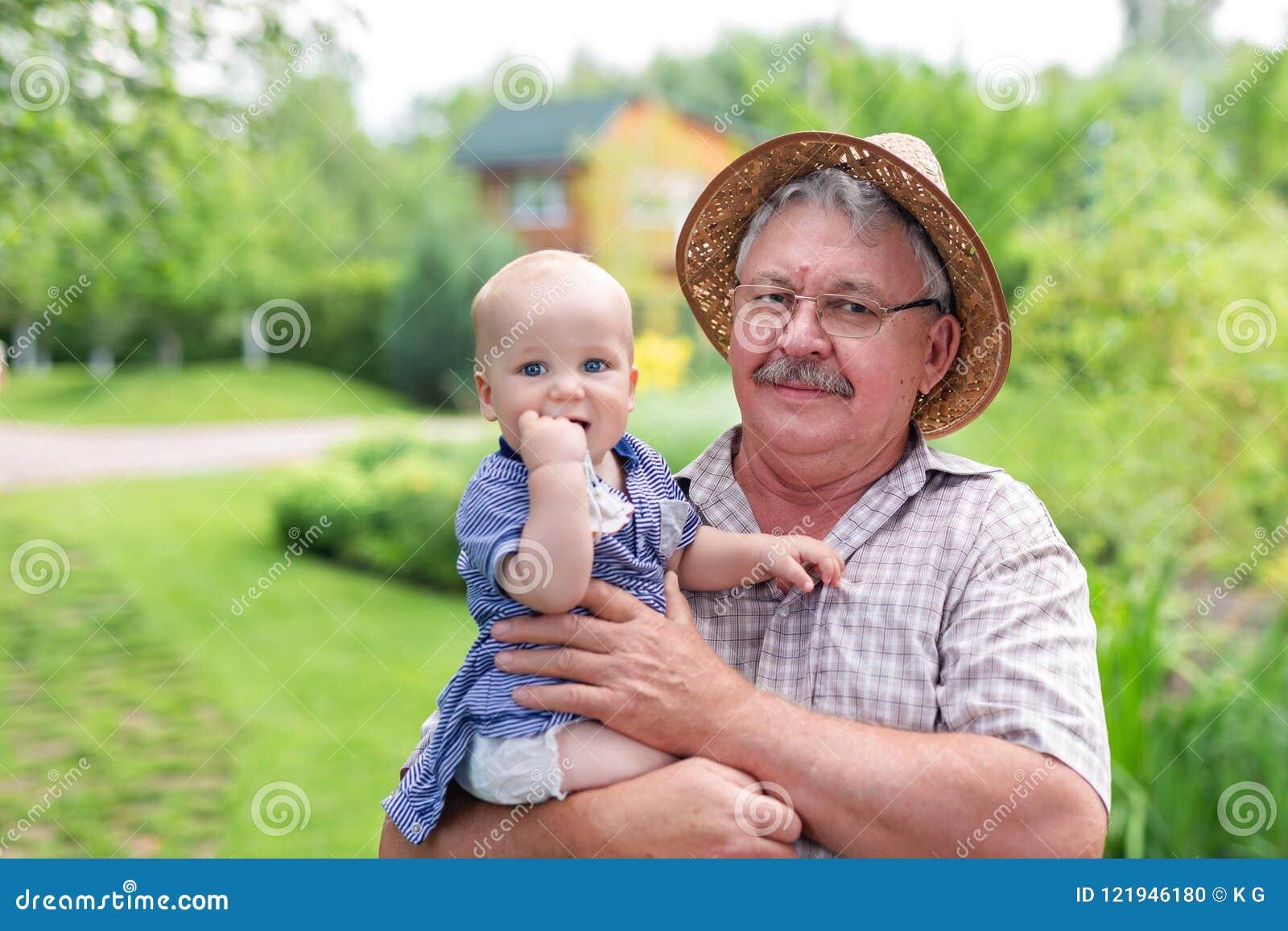 Homme gris supérieur dans le chapeau de paille tenant le petit-fils en main et ayant l amusement dans le jardin vert d été Bébé g