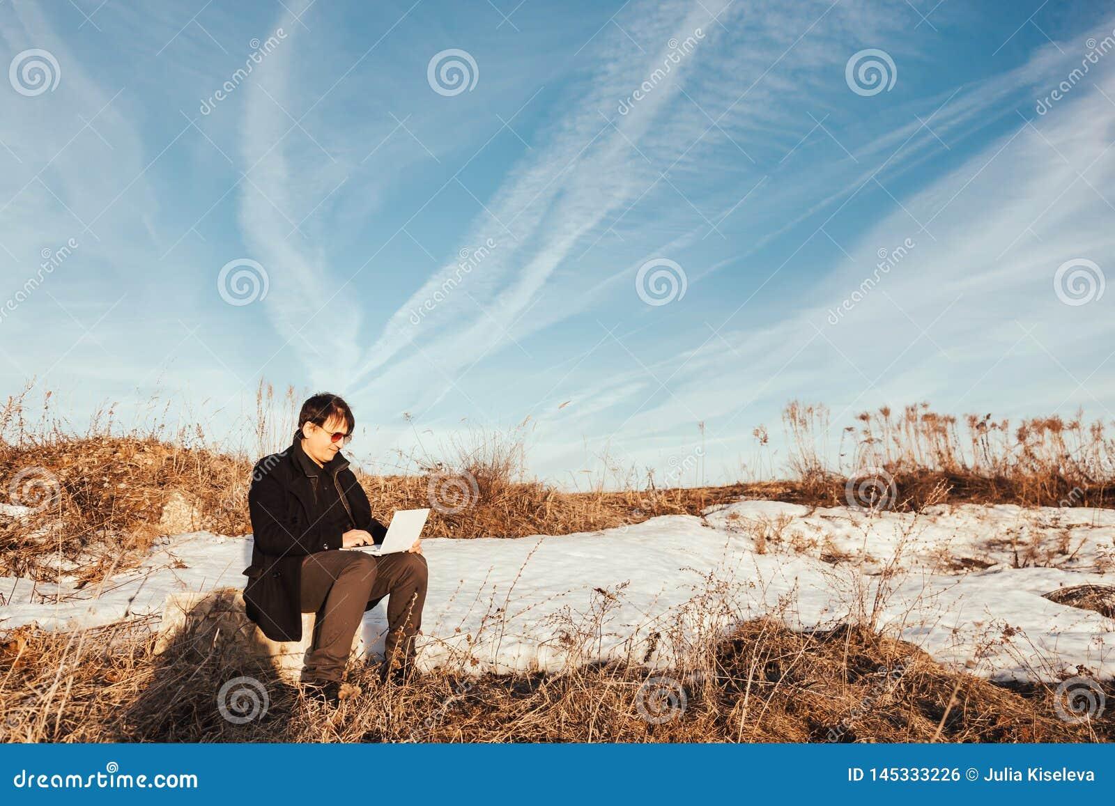 Homme heureux avec l ordinateur portatif dans le domaine de bl?