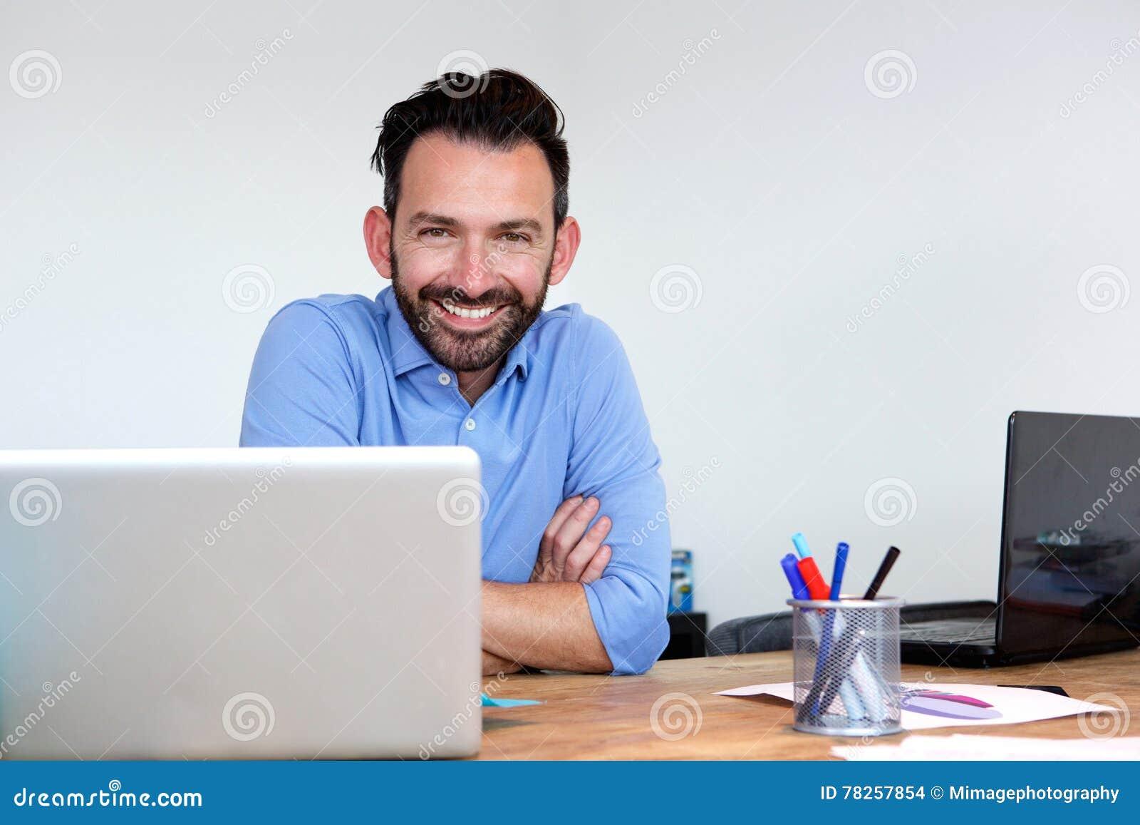 Homme heureux d affaires mûres s asseyant à son bureau