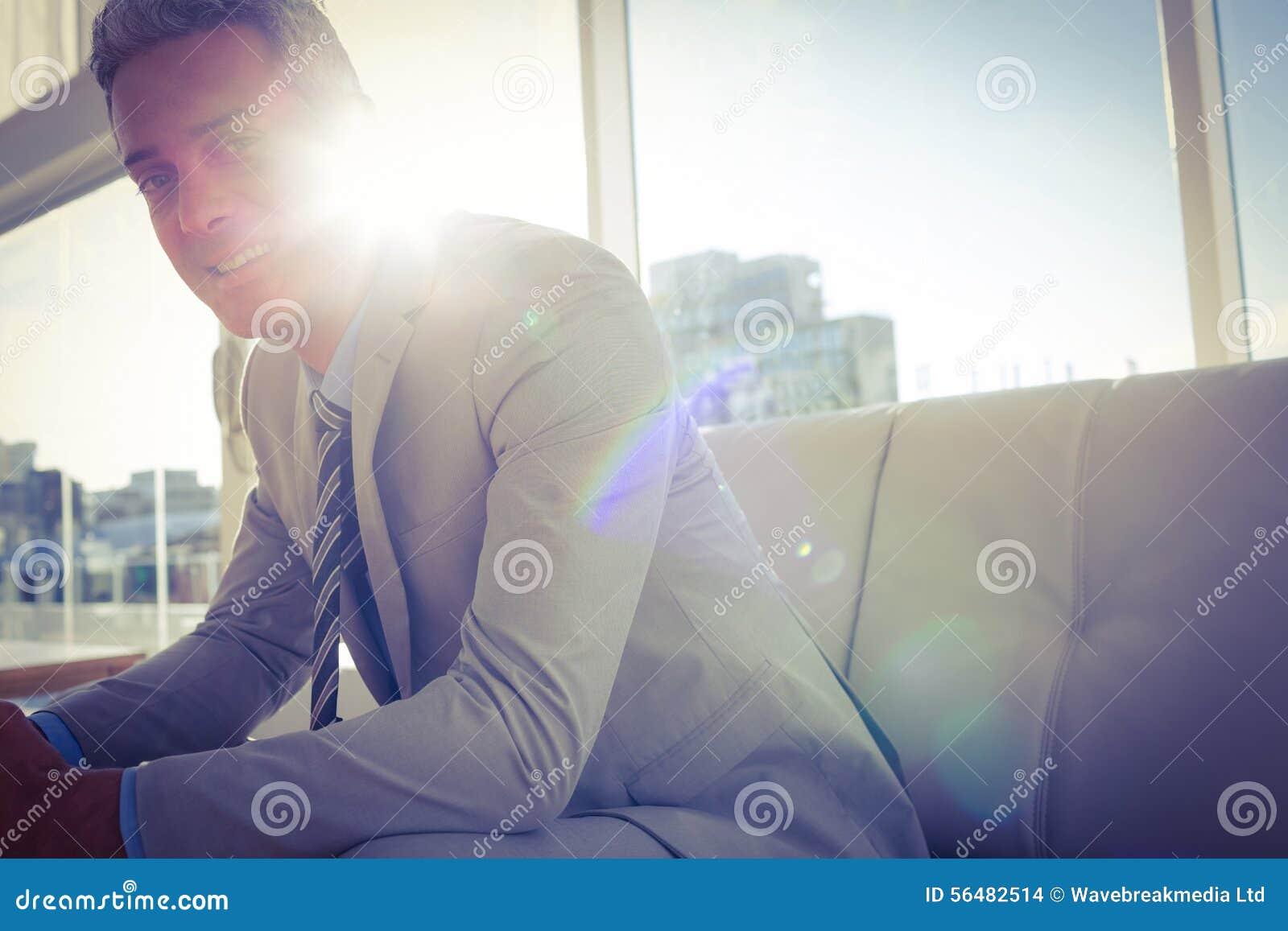 Homme heureux d affaires s asseyant sur le sofa et regardant l appareil-photo