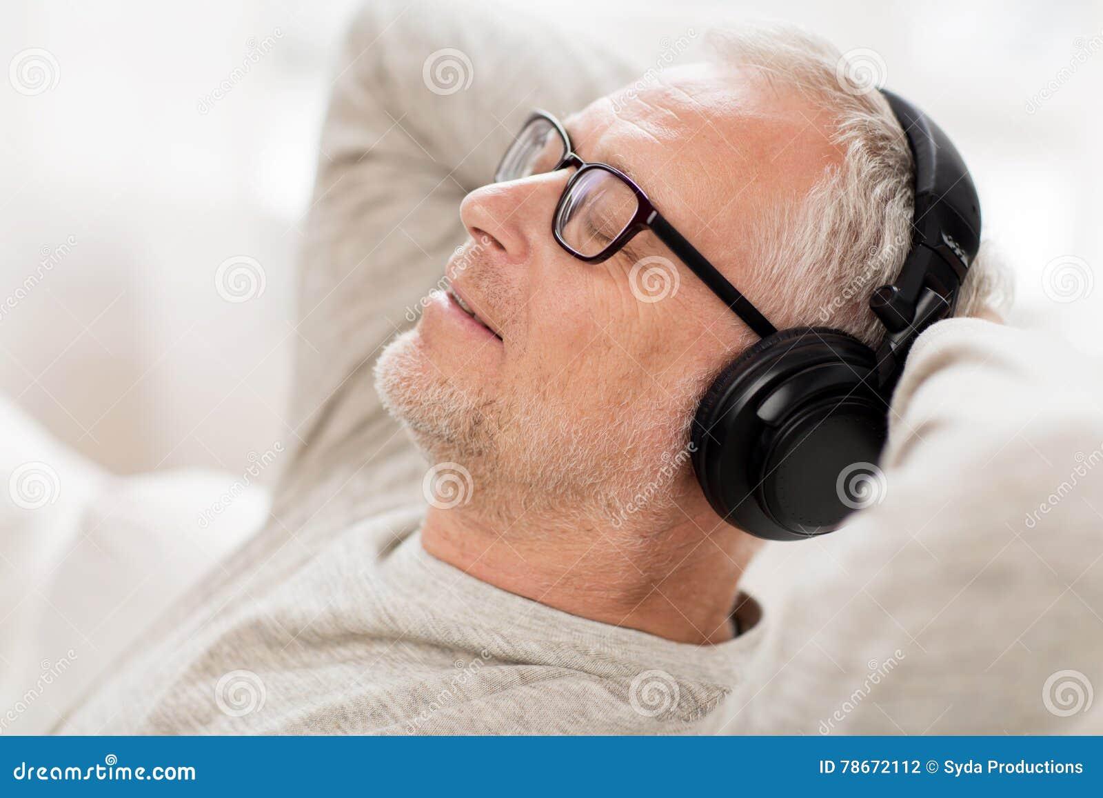 Homme heureux dans des écouteurs écoutant la musique à la maison