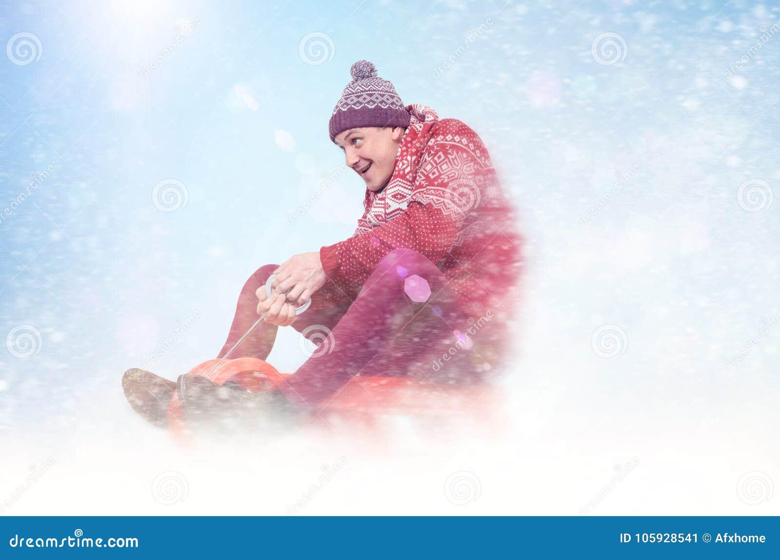 Homme heureux dans sledding rouge de chandail et de chapeau L hiver, le soleil, neige, évase