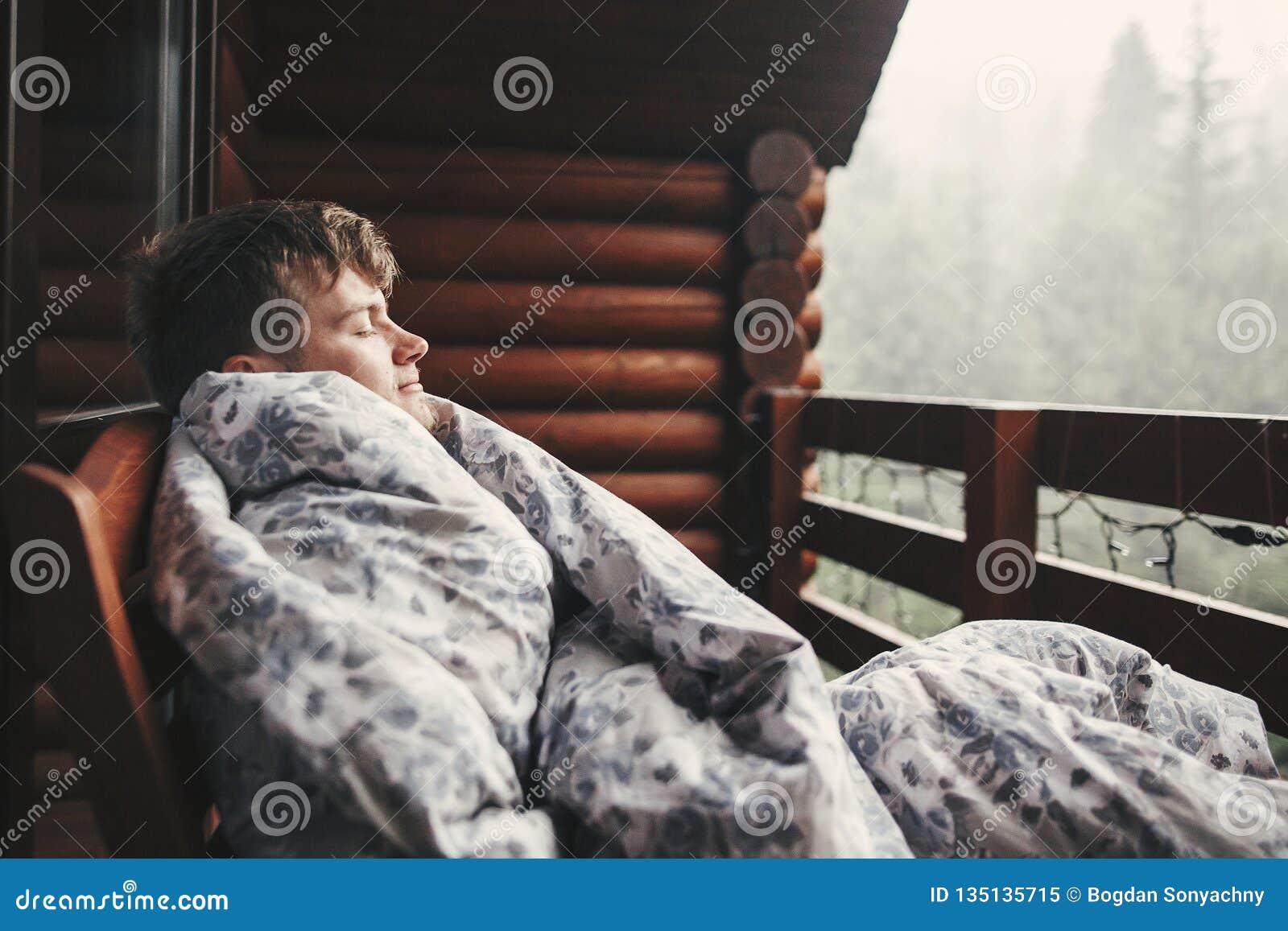 Homme heureux de voyageur se reposant dans la couverture sur le porche en bois avec la vue sur des bois et des montagnes L espace