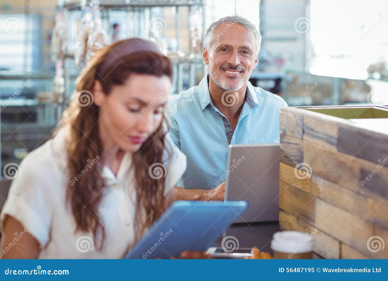Homme heureux regardant l appareil-photo et à l aide de l ordinateur portable