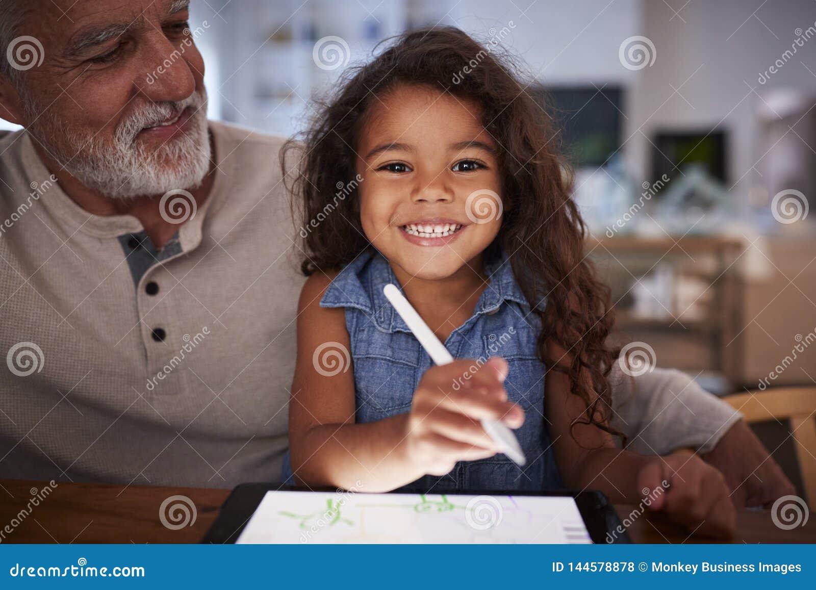 Homme hispanique supérieur avec sa jeune petite-fille à l aide du stylet et de la tablette, souriant à la caméra